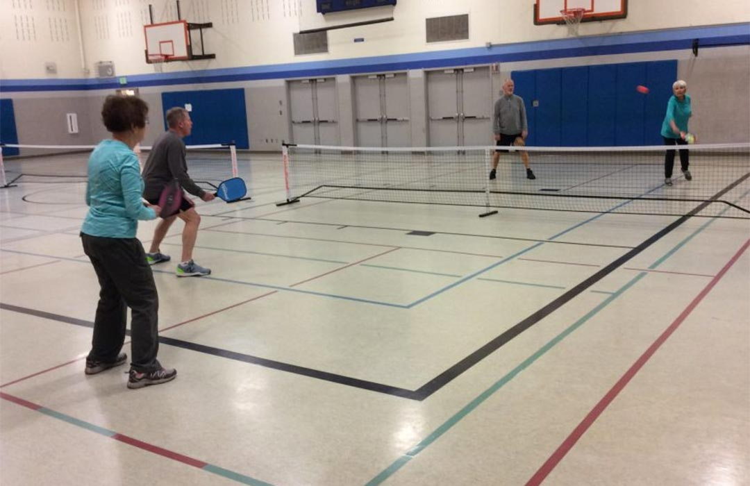 Two teams of two people playing pickleball in a gym
